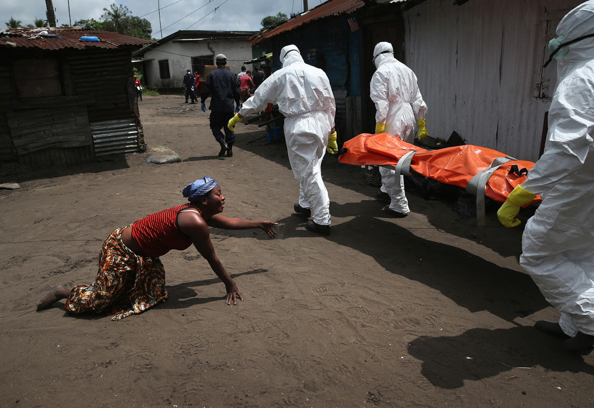 A woman crawls towards the body of her sister as Ebola burial team members take her away.